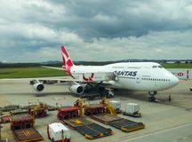 在柏油碎石地面的Quantas飞机在机场在多云天空下在布里斯班昆士兰澳大利亚11 23 2013年 免版税库存照片
