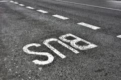 在柏油碎石地面路的公共汽车符号 免版税图库摄影