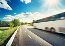 在柏油路的公共汽车在美好的春日 免版税库存图片