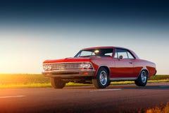 在柏油路的减速火箭的红色汽车逗留在日落 免版税库存图片