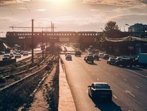 在柏油路的城市交通在日落时间,全部汽车驾驶与最快速度,被弄脏的都市运输都市风景 库存照片