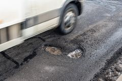 在柏油路的大孔,通过blury汽车 库存图片