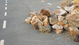 在柏油路的岩石幻灯片 库存照片