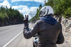 在柏油路的摩托车驾驶员背面图,坐摩托车和显示胜利标志机智手 库存图片