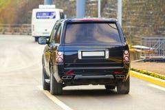 在柏油路的新的黑色SUV汽车停车处 库存照片