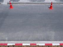 在柏油路的橙色塑料交通锥体相对于红色白线条乐团 库存照片