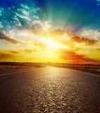 在柏油路的橙色日落 库存图片