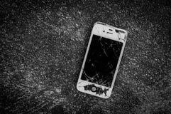 在柏油路的残破的iPhone 4S有小插图作用的 免版税库存图片