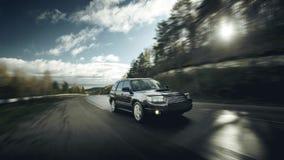 黑在柏油路的汽车快速的驱动在白天 免版税库存图片