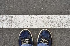 在柏油路的男性鞋子有空白线路的,步到里 库存图片
