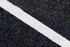 在柏油路的白色对角标号线 免版税库存图片