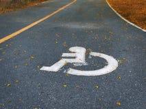 在柏油路的白色有残障的标志在公园 免版税库存图片