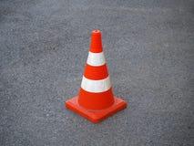 在柏油路的红色和白色镶边交通锥体 库存照片