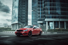 在柏油路的红色汽车逗留在白天的城市 库存图片