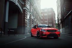 在柏油路的红色汽车逗留在白天的城市 库存照片