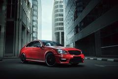 在柏油路的红色汽车逗留在白天的城市 免版税库存照片
