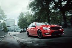 在柏油路的红色汽车驱动在白天的城市 免版税库存照片