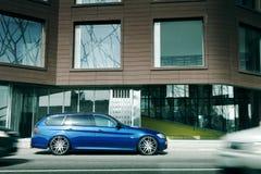 在柏油路的蓝色汽车逗留在城市 库存图片