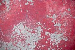 在柏油路的被风化的红色膏药 背景的混凝土墙脏的纹理照片 红色油漆和困厄的污点 免版税库存照片