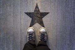 在柏油路的运动鞋有白色黑形状的 库存图片