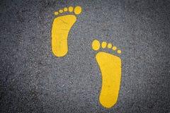 在柏油路的黄色脚印标志 库存照片