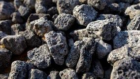 在柏油路边缘的石头 免版税库存照片