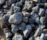在柏油路边缘的石头 图库摄影