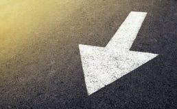 在柏油路,交通标志的白色箭头 库存图片