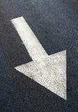 在柏油路,交通标志的白色箭头 免版税库存图片