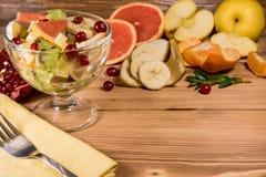 在柑橘和果子旁边节食在一块玻璃板在一张木背景桌上与餐巾和一把叉子的新鲜的沙拉对此 戒毒所食物 库存图片