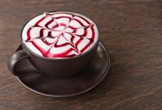 在柚木树木头表的一个咖啡Latte艺术 库存照片