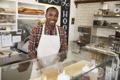 在柜台后的人在看对照相机的三明治酒吧 免版税库存图片