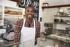 在柜台后的企业主在三明治酒吧 免版税图库摄影