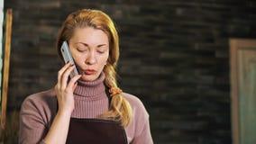 在柜台后的妇女卖花人谈话在电话和看片剂的 影视素材
