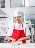 在柜台的微笑的女性厨师揉的面团 免版税库存图片