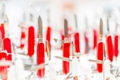 在柜台的红色折叠的刀子 免版税库存图片