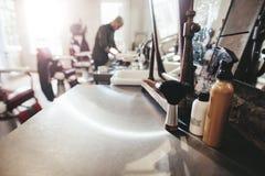 在柜台的美发师工具在理发店 免版税库存图片