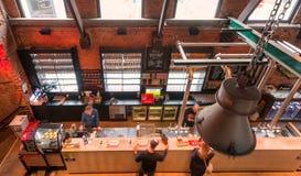 在柜台的顶视图与在历史啤酒厂里面的啤酒饮用的人民有商标的De Koninck 免版税库存图片