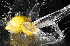 在柠檬的淡水下落在黑色 免版税库存照片