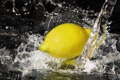 在柠檬的淡水下落在黑色 图库摄影