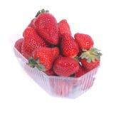 在查出的一个塑料盒的新鲜的水多的草莓 免版税库存照片