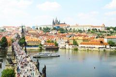 在查尔斯桥梁有许多人民的和布拉格城堡的美丽的景色在背景中 库存图片