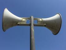 在柱子的两台扩音器在蓝天背景中 库存图片