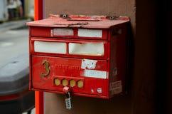 在柱子的被风化的红色岗位箱子与号码锁 免版税图库摄影