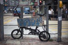 在柱子附近的老自行车在街道上 图库摄影
