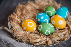 在柳条巢的五颜六色的鸡蛋 免版税图库摄影