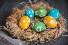 在柳条巢的五颜六色的鸡蛋 图库摄影