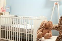在柳条扶手椅子的逗人喜爱的兔宝宝玩具 库存照片