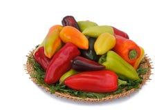 在柳条盘的红色,黄色和青椒在白色后面 图库摄影