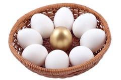 在柳条碗的金黄蛋和jast鸡蛋在白色 免版税库存图片
